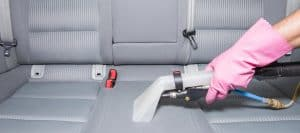 cleaner cleaning upholstery in a car