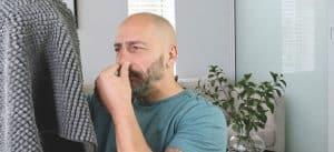 man smelling carper while pinching his nose